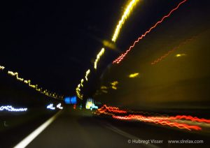 Highway at night shot from a car using a slow shutter speed showing blurred light trails