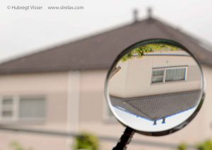 A magnifying glass showing trhe flipped image of a house on a far distance